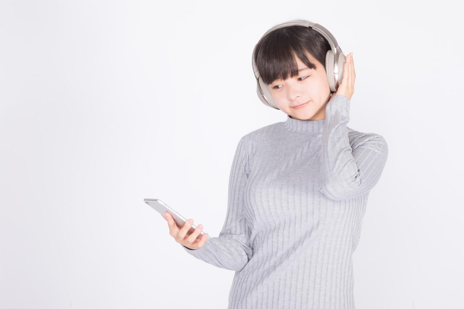 「ワイヤレスヘッドホンで音楽を楽しむ若い女性」の写真[モデル:千歳]
