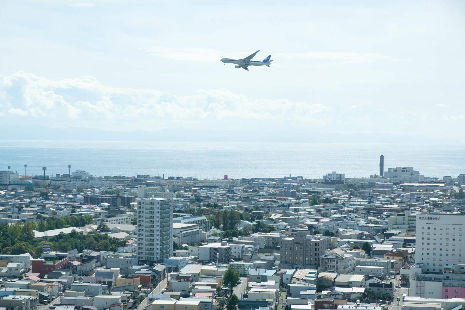 「街並みと離陸した旅客機(函館空港)」の写真