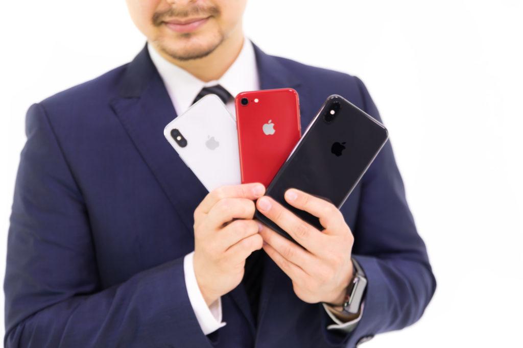 「歴代iPhone三機種を見せびらかすビジネスマン | ぱくたそフリー素材」の写真[モデル:Max_Ezaki]