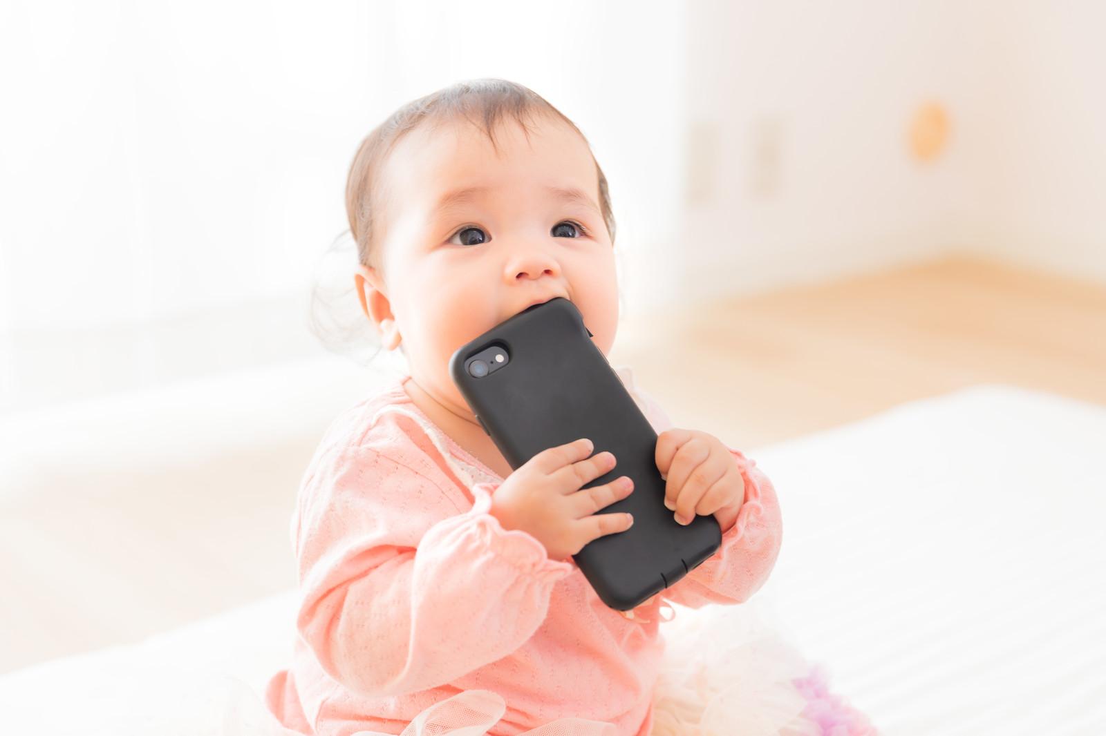「スマートフォンを口に入れてしまう赤ちゃん」の写真[モデル:めぐな]