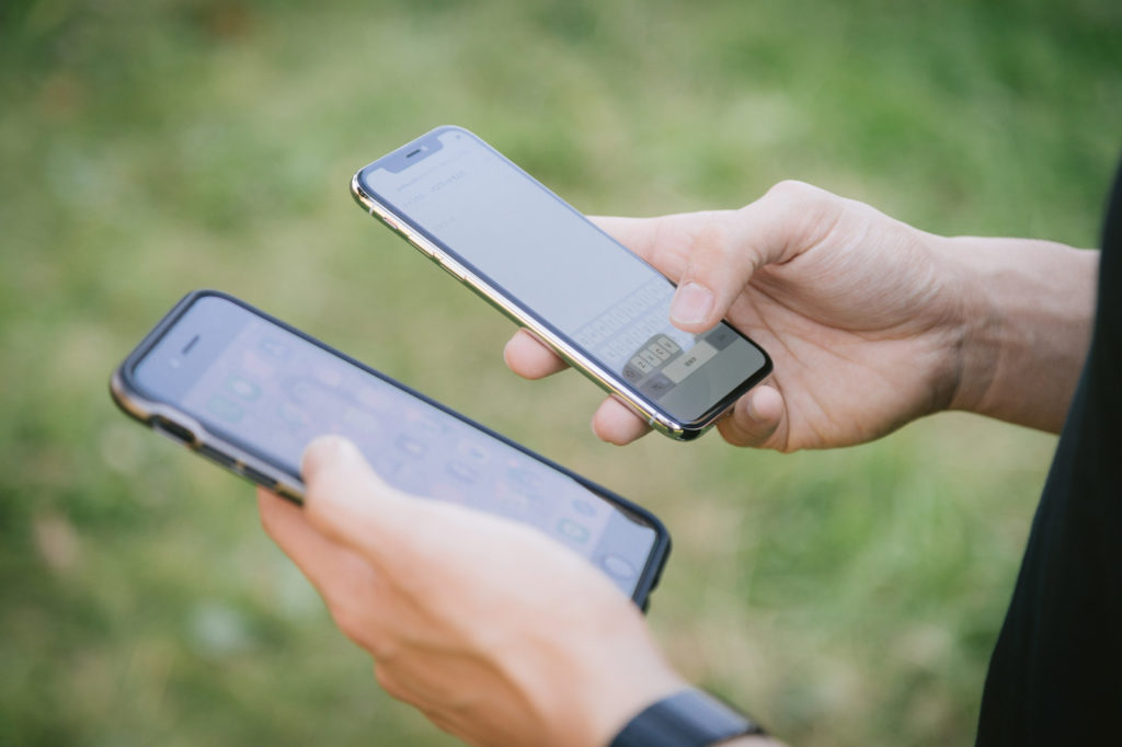 「2台のスマホ(iPhone)を操作する男性の手 | ぱくたそフリー素材」の写真