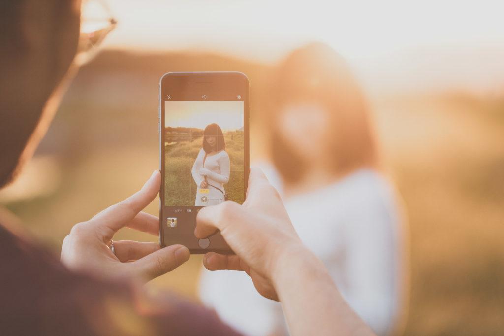 「逆光の中、iPhone 8 のポートレートモードでグラドルを撮影中のブロガー | ぱくたそフリー素材」の写真[モデル:茜さや]